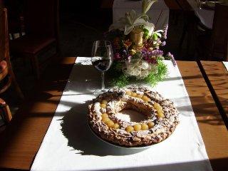 Roscón de Reyes hecho con una masa de hojaldre relleno de crema pastelera, chocolate negro. Untado con huevo y espolvoreado con azúcar moreno. Decorado con almendras laminadas, uvas peladas sin pepitas, nueces y espolverado con azucar glacé.